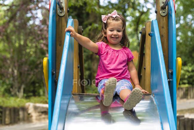 Retrato de niña sonriente en el tobogán del patio - foto de stock