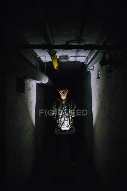 Человек, держащий подсветку смартфона в темном коридоре посреди старых стен — стоковое фото