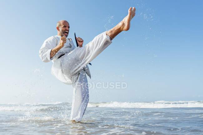 Hombre maduro gritando mientras practica karate en el mar contra el cielo despejado - foto de stock