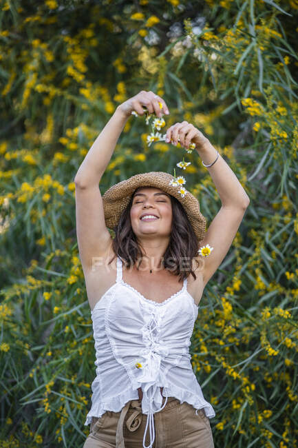 Smiling beautiful young woman making flowers fall on her, Alicante, Alicante Province, Spain — Stock Photo