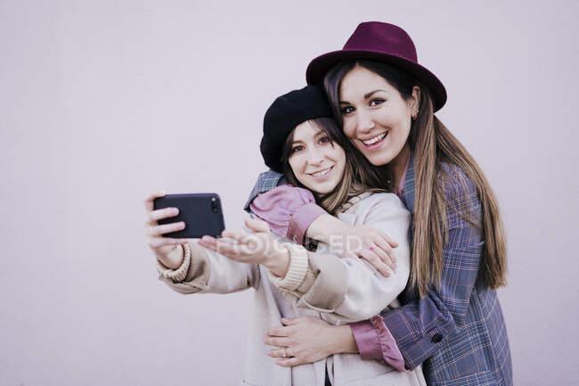 Retrato de dos mujeres felices tomando selfie con smartphone - foto de stock