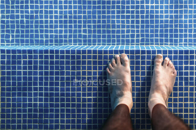 Feet of man standing ankle deep in swimming pool — Stock Photo