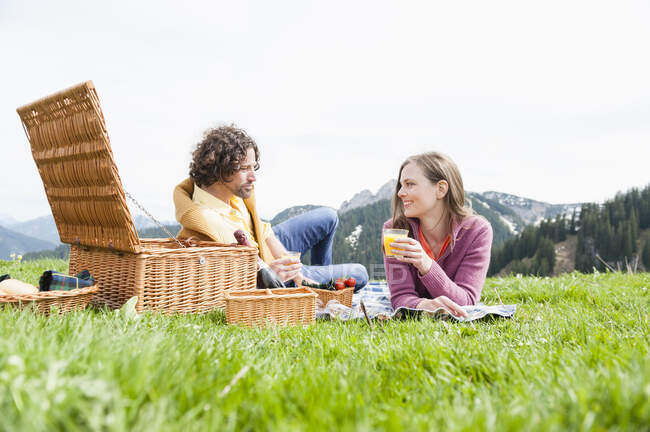 Mid adult couple enjoying picnic while lying against clear sky — Stock Photo