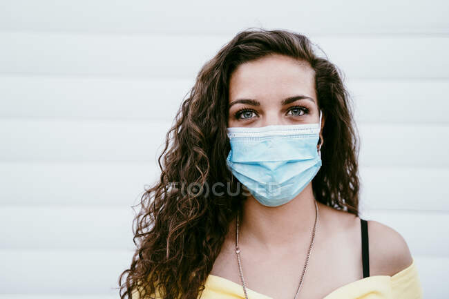 Close-up of young woman wearing mask against wall in city — Stock Photo