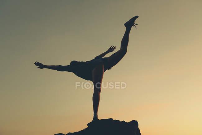 Женщина, стоящая на одной ноге на пляже во время заката — стоковое фото