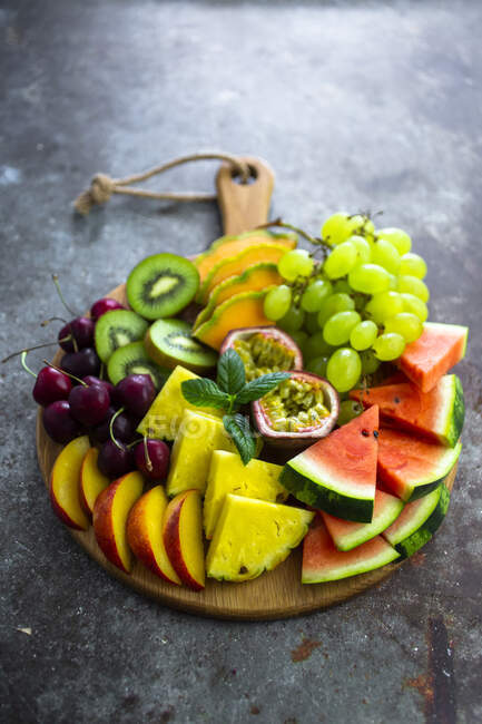 Ensalada de frutas con sandía, kiwi, fruta de la pasión, uva, cereza, melocotón y melón en la tabla de cortar - foto de stock