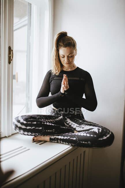 Женщина медитирует на подоконнике дома — стоковое фото