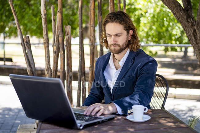 Bonito homem profissional usando laptop enquanto sentado com xícara de café no café — Fotografia de Stock