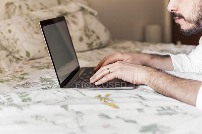 Hombre usando portátil en la cama - foto de stock