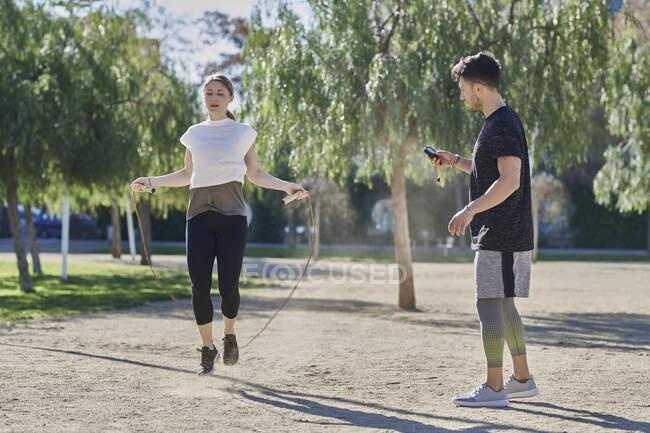 Mujer durante el entrenamiento con el entrenador saltar la cuerda en el parque - foto de stock