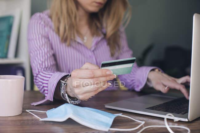 Бизнесвумен, держащая кредитную карту, производит онлайн-оплату за ноутбук в офисе — стоковое фото