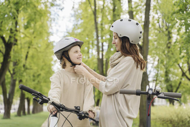 Mother wearing helmet to her daughter against trees in city park — Stock Photo