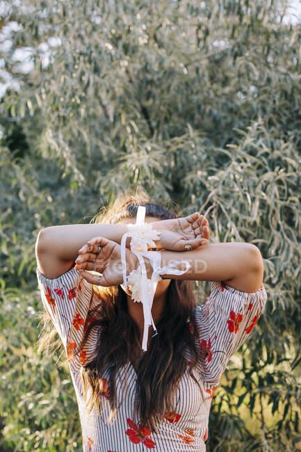 Nahaufnahme einer Frau mit Blumen und Bändern an den Händen, die gegen Pflanzen im Park steht — Stockfoto