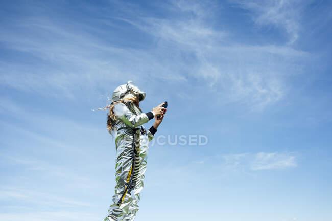 Vista de ángulo bajo de la chica en traje espacial utilizando el teléfono inteligente mientras está de pie contra el cielo azul - foto de stock