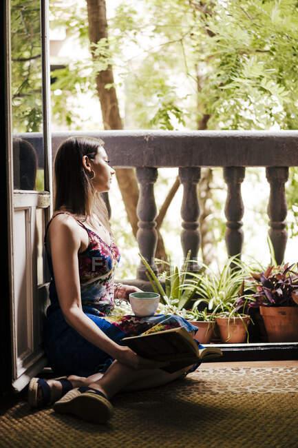 Mujer sosteniendo taza y libro mientras está sentado en el balcón en casa - foto de stock