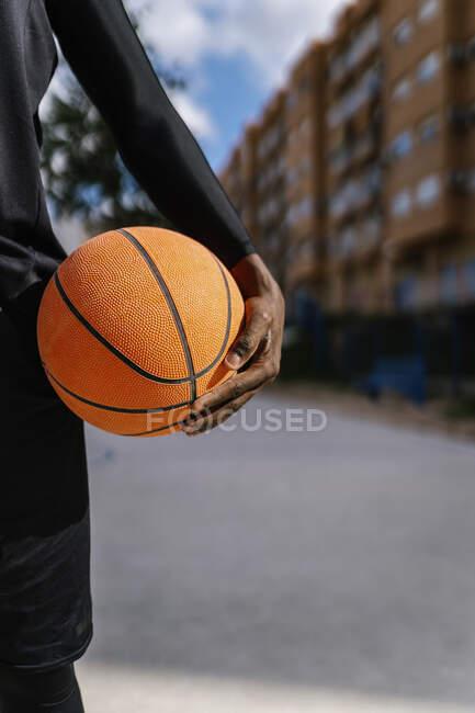 Молодий чоловік тримає баскетбол на баскетбольному майданчику. — стокове фото