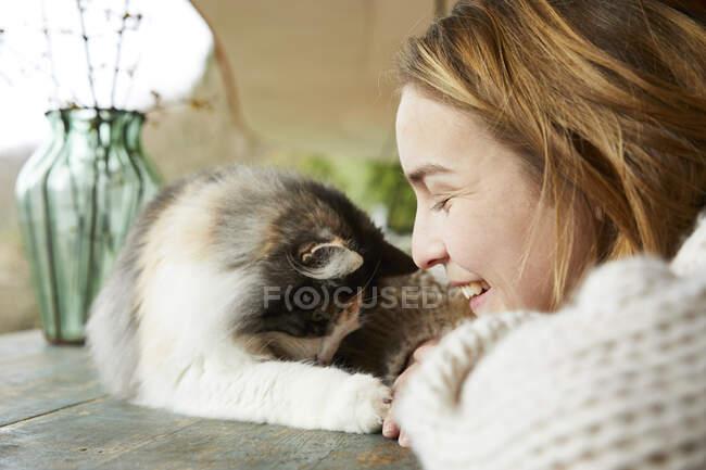 Mujer feliz con gato bosque noruego en mesa de madera al aire libre - foto de stock