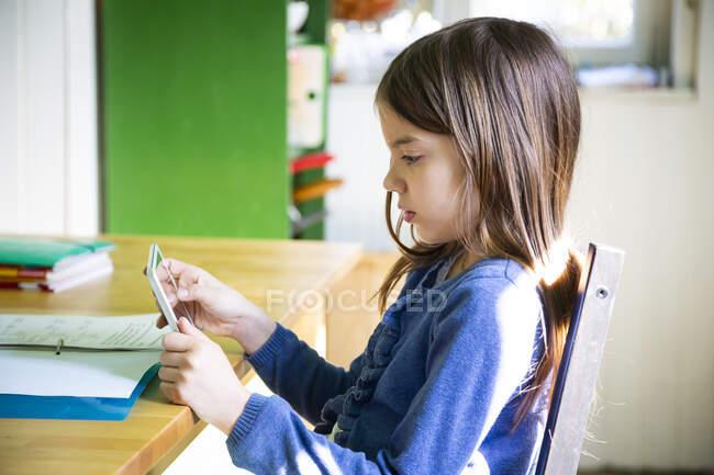 Chica haciendo los deberes y el uso de la tableta en la cocina en casa - foto de stock