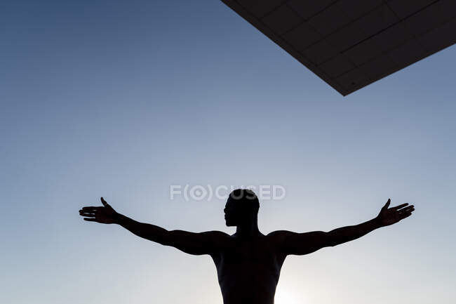 Silhouette of man stretching out arms, against clear sky — Stock Photo