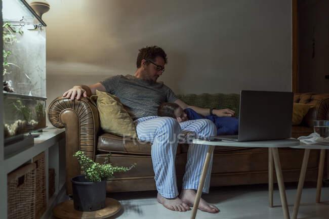 Mann sitzt bei kranker Tochter und schläft während Quarantäne auf Sofa im Wohnzimmer — Stockfoto