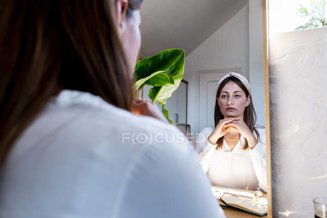 Beautiful woman looking at self in mirror reflection — Stock Photo