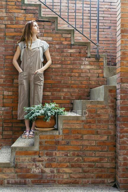 Mulher pensativa olhando para cima enquanto em pé em passos — Fotografia de Stock