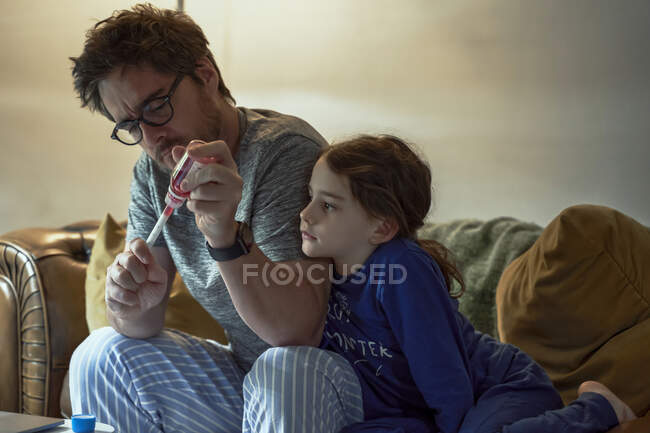 Chica enferma mirando a padre preparando medicina para ella mientras está sentado en la sala de estar en casa - foto de stock