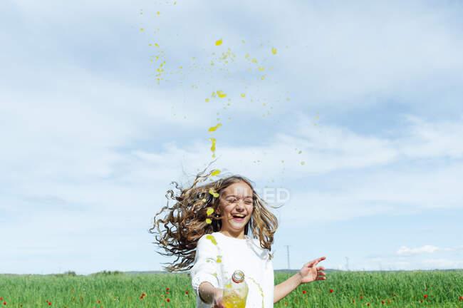 Ragazza allegra spruzzando succo di bottiglia mentre godendo contro il cielo nella giornata di sole — Foto stock