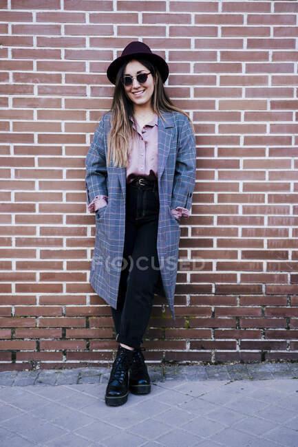 Retrato de la mujer de moda de pie frente a la pared de ladrillo - foto de stock