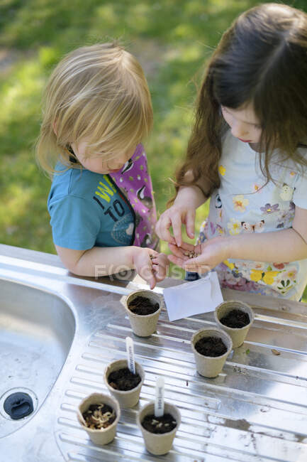 Girls planting seeds in small pots on table at garden — Stock Photo