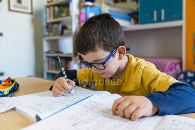 Elementary student learning while sitting at desk during homeschooling — Stock Photo