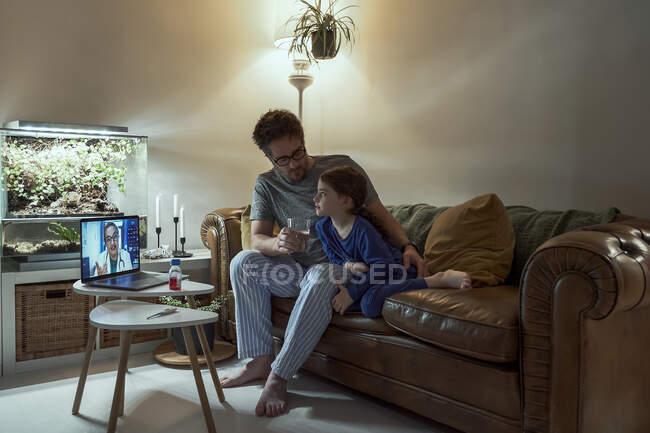 Arzt auf Videoanruf mit krankem Mädchen und ihrem Vater über Laptop zu Hause — Stockfoto