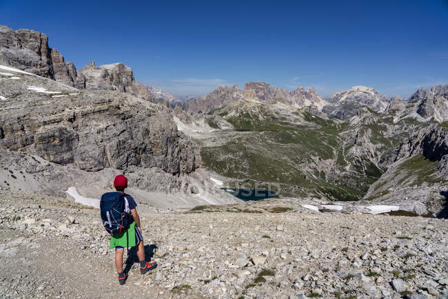 Вид сзади мальчика с рюкзаком, смотрящего на Тре Крунур ди Лаваредо на фоне голубого неба, Озил, Италия — стоковое фото
