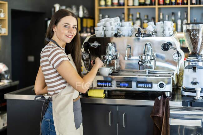 Счастливая бариста с кофеваркой в кафе — стоковое фото