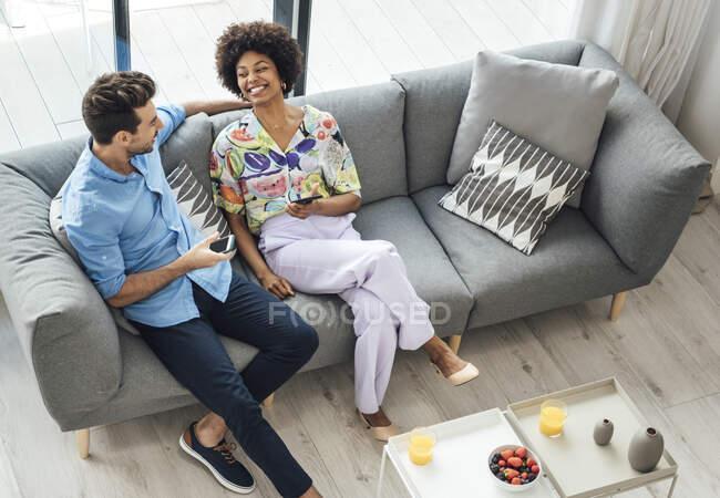 Felice coppia multietnica in possesso di smartphone mentre si siede sul divano in attico — Foto stock