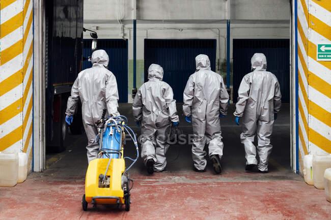Vista trasera de los compañeros de trabajo de saneamiento que ingresan al almacén con descontaminación química - foto de stock