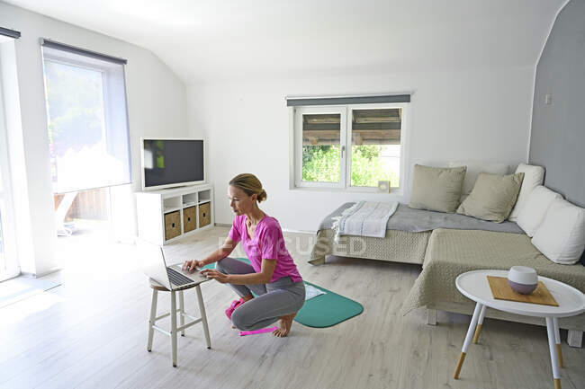 Зріла жінка з ноутбуком практикує йогу на спортивному мат у вітальні. — стокове фото