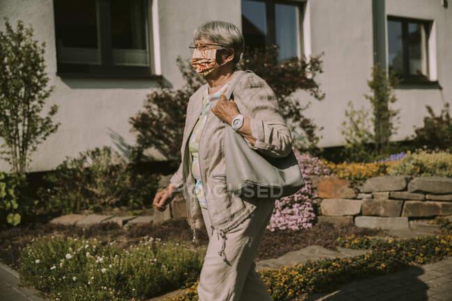 Mujer mayor caminando al aire libre en un día soleado durante el coronavirus - foto de stock