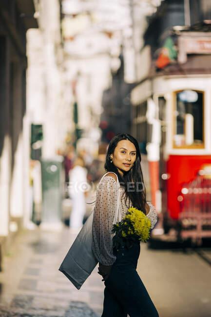 Mujer joven con ramo de caminar en la ciudad - foto de stock