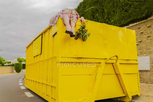 Woman lying on top of yellow container, holding buch of flowers — Stock Photo