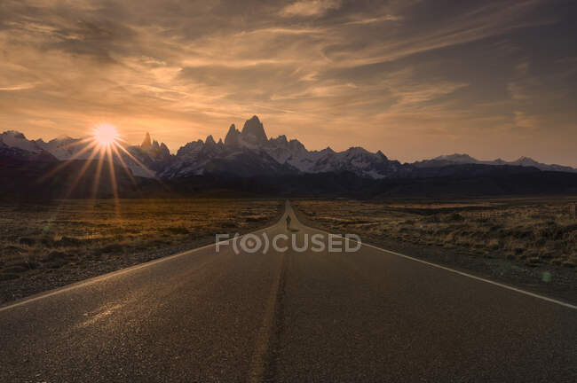 Homem caminhando na estrada para El Chalten ao pôr do sol, Patagônia, Argentina — Fotografia de Stock