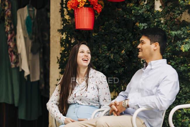 Веселая беременная женщина, сидящая с мужчиной в солнечный день — стоковое фото