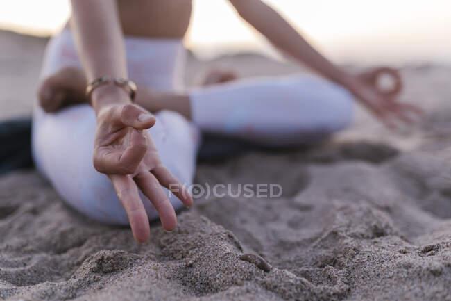 Крупный план молодой женщины, медитирующей на песке на пляже — стоковое фото