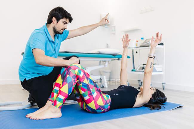 Физиотерапевт с нарушением зрения инструктирует женщину в упражнениях в клинике — стоковое фото
