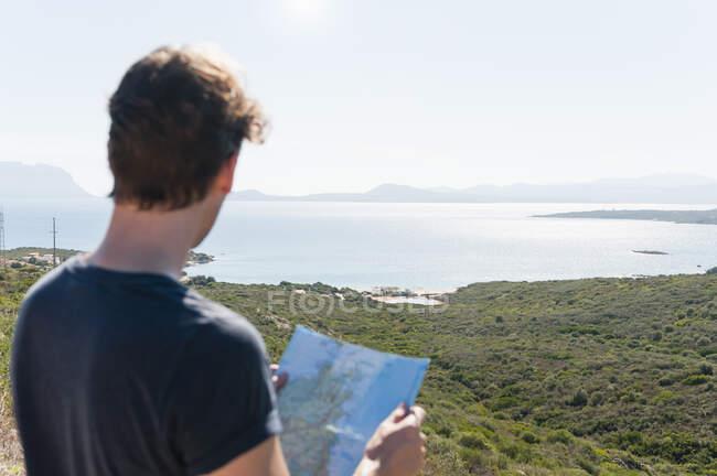 Visão traseira do homem com mapa olhando para a vista, Sardenha, Itália — Fotografia de Stock