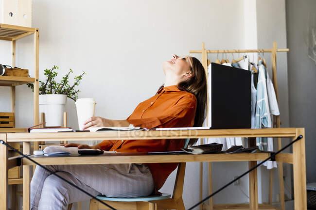 Жінка-модельєр вдома сидить за столом, спираючись на спину. — стокове фото