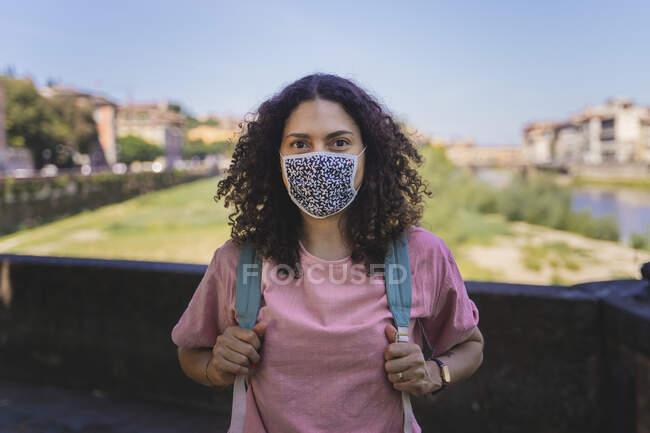 Mulher usando máscara protetora em pé com mochila na cidade contra o céu — Fotografia de Stock