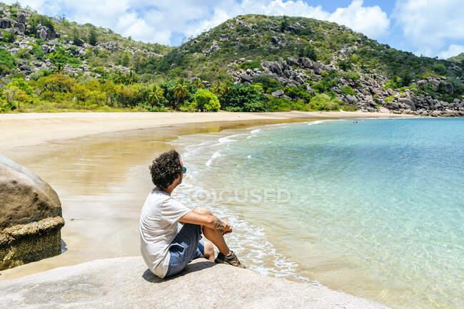Hombre sentado en la roca en Magnetic Island, Queensland, Australia - foto de stock