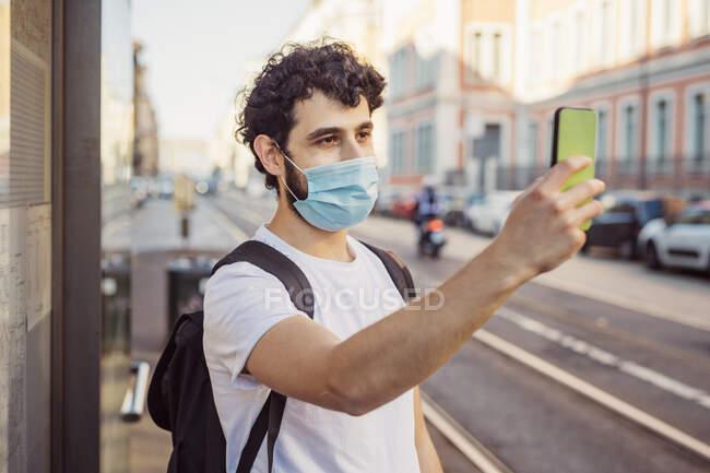 Jovem usando máscara tirando selfie com telefone inteligente enquanto estava na cidade — Fotografia de Stock