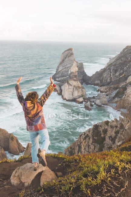 Giovane donna con le braccia alzate sulla roccia a Ursa Beach, Regione di Lisboa, Portogallo — Foto stock